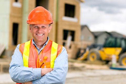 Builder with Hardhat in Front of Construction Site